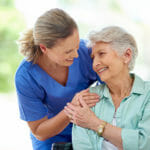 nurse-holding-senior-woman-and-smiling