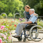 Assisted living – caregiver and senior man on a wheelchair