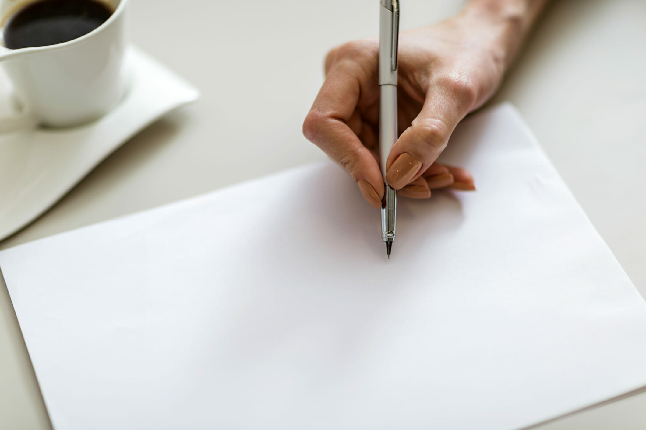 Close-up of female hand writing on blank piece of paper with cup of coffee in background