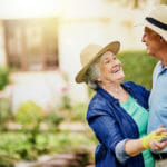Senior man and woman smiling and dancing in their backyard while wearing sunhats and gardening gloves