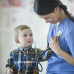 A little boy is using a stethoscope to listen to the nurses heartbeat.