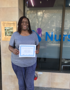 female nurse poses with certificate award in front of nurseregistry office building