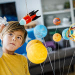 Little boy playing with solar system in classroom.