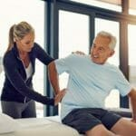 Adult man undergoing physical therapy program with his physical therapist