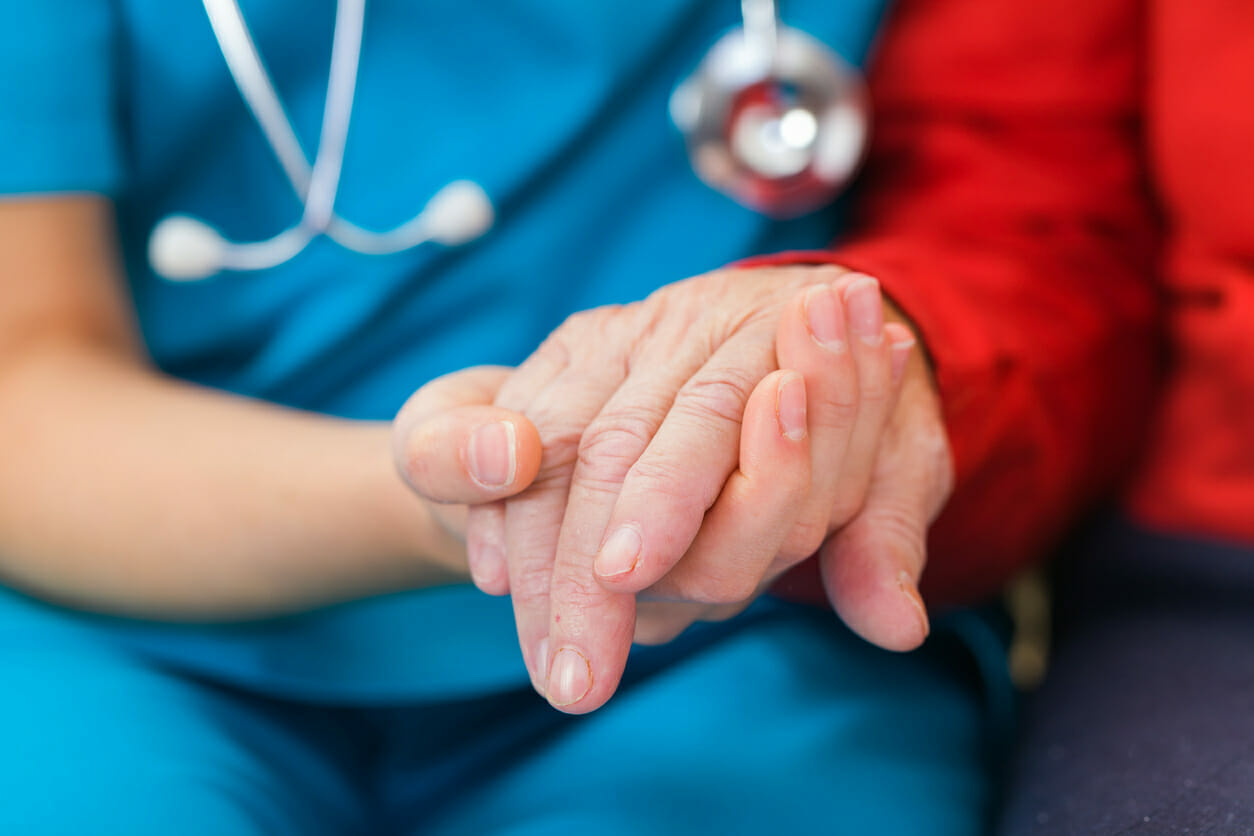 Nurse holding hands with an Alzheimer's patient