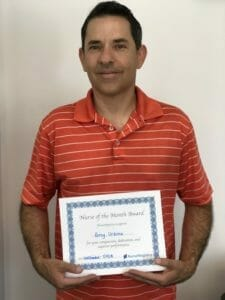 Greg Urbina RN, NurseRegistry Nurse of the Month for June, smiling in orange tshirt