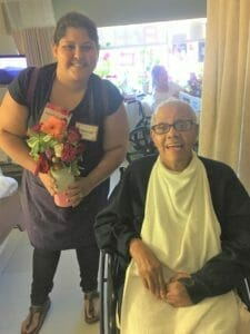 volunteer handing flowers to resident at los altos subacute and rehabilitation center