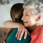 older-woman-hugging-daughter-in-pain