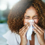 woman-sneezing-into-tissue