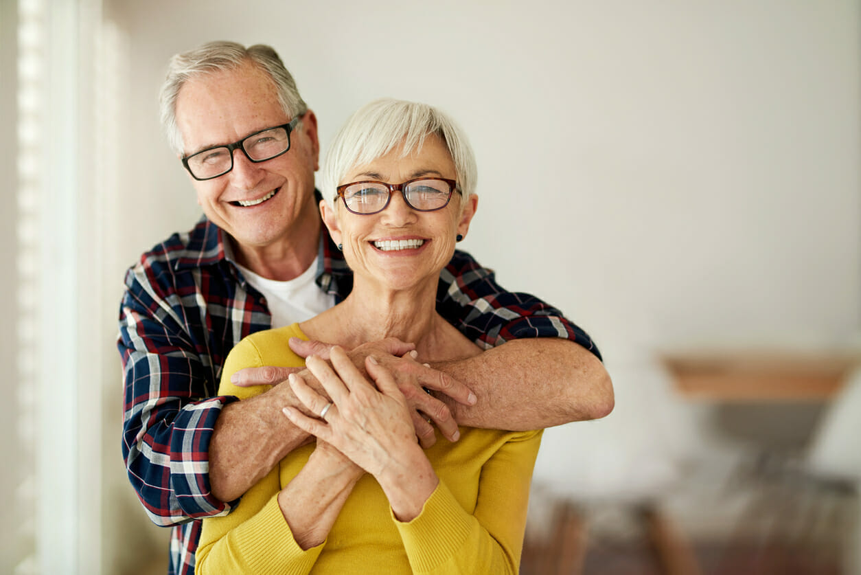 senior man and woman hugging and smiling
