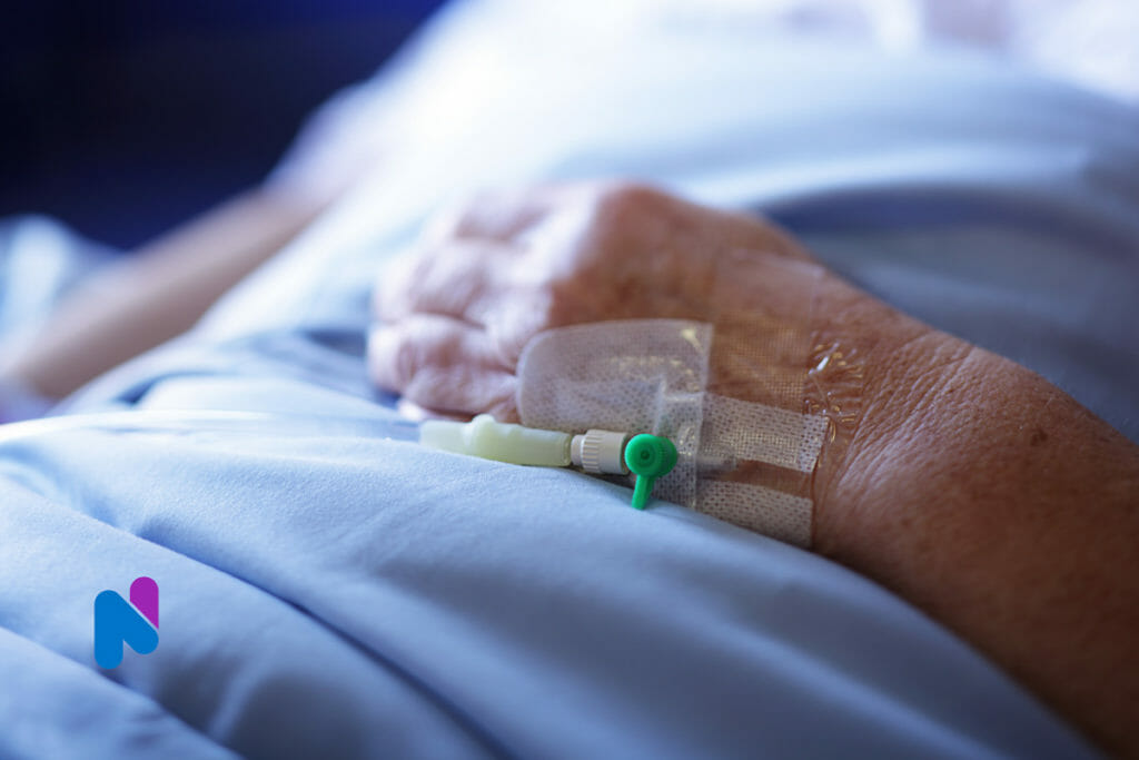 Intensive Care Unit ICU patient with iv in hand in hospital bed