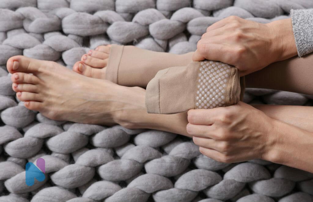 woman putting on compression socks