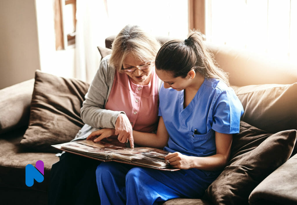 older senior adult with nurse at home looking at photo album memories