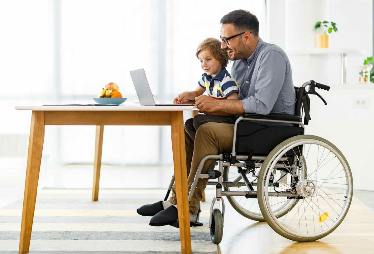father sitting in rental wheelchair with son in his lap