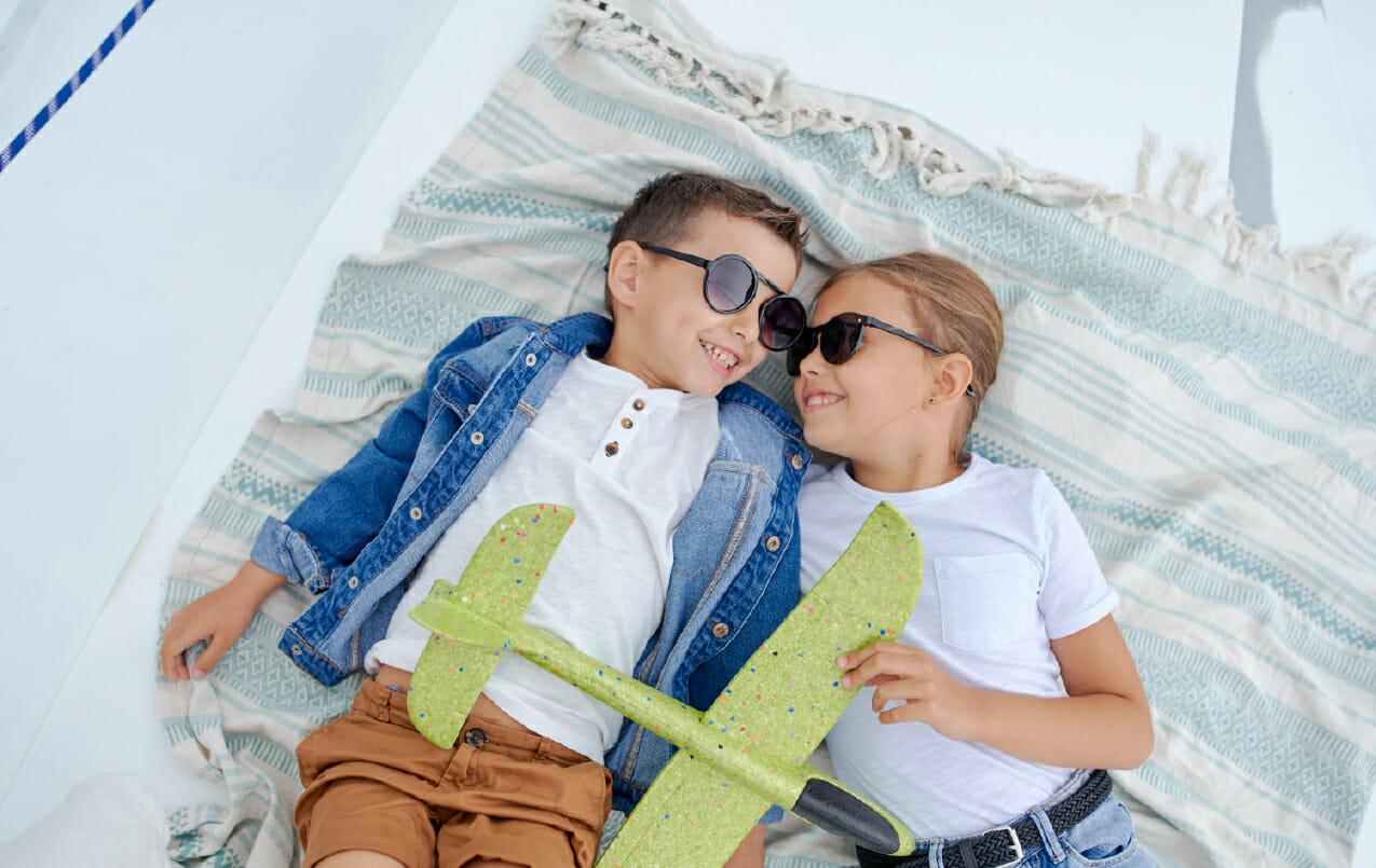 children playing and relaxing in the summer sun wearing sunglasses